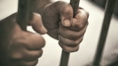 Prisoner's hands clasped around prison bars