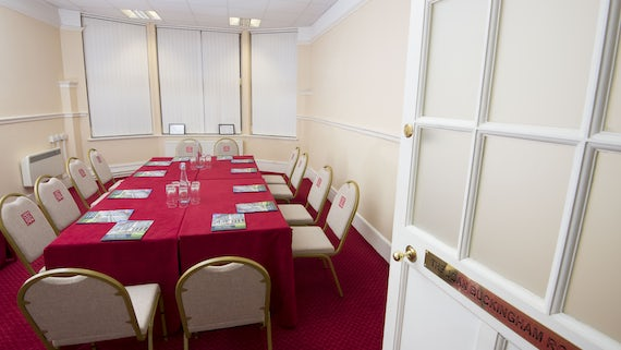 Joan Buckingham Room set up for a meeting, with red tablecloth, papers and water glasses, flipchart in corner