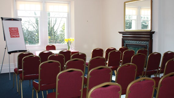 Room set out in theatre style, with chairs in rows and a table and flipchart at front.