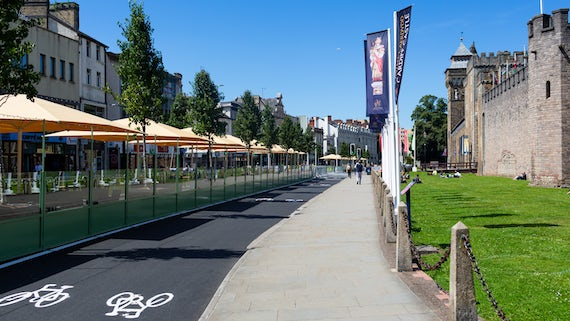 Cardiff Castle Street with cycle lane, castle and outdoor cafe area on a sunny day. Photo credit: FOR Cardiff.