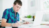Teenage boy using laptop and doing homework - stock photo