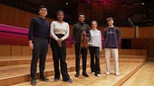 Violinist Randall Goosby posing in front of a piano with students.