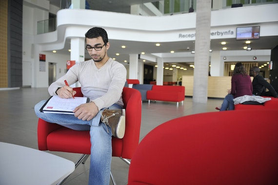 Male student hands holding pen, completing postgraduate application form