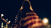 Woman draped in US flag at night