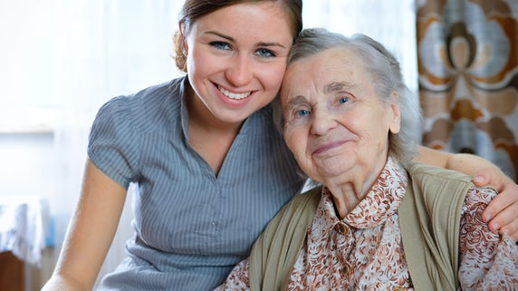 Photograph of a young woman with her arm around an older relative
