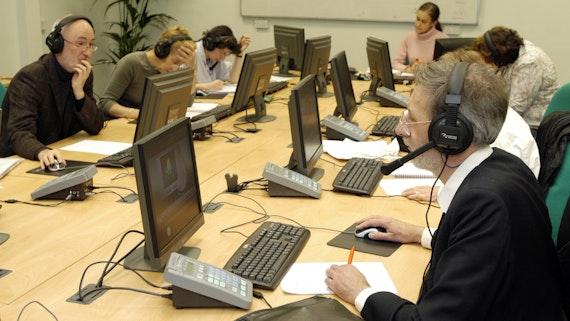 Students in an IT room wearing headphones
