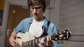 Student at Cardiff University School of Music playing guitar