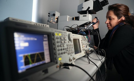 Research worker in optics lab