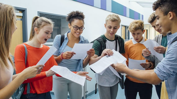 Group of sixth form students looking excited and happy as they read their exam results