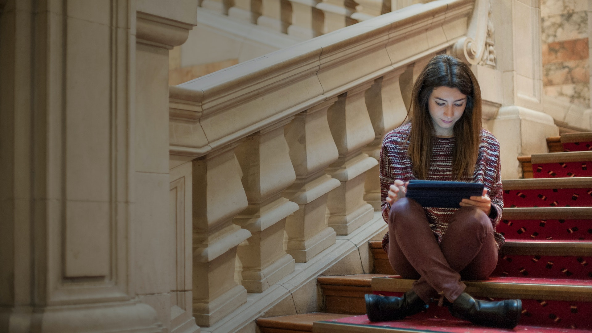 Female student sat cross legged on the steps of Main Building looking at a tablet