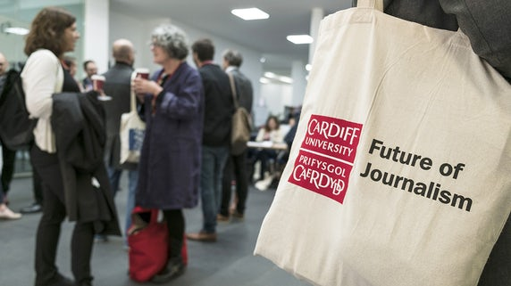 A person holds a bag with Future of Journalism written on it at the 2017 conference.