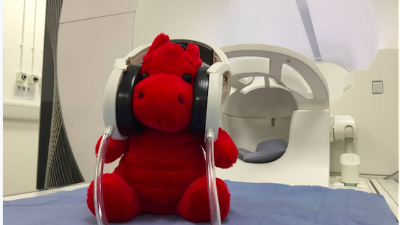 The mascot Dylan the red dragon sat on top of the bed of the MRI scanner wearing headphones