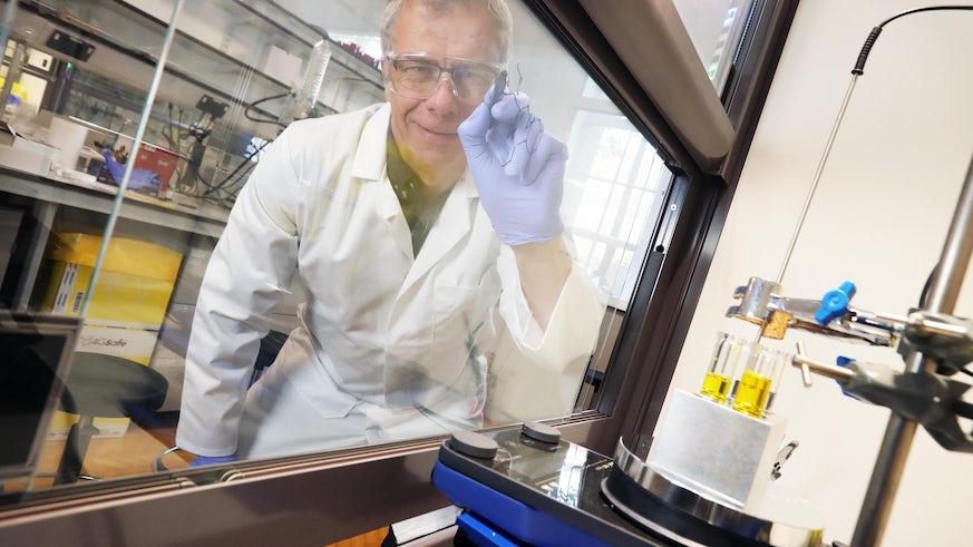 Professor John Atack writing chemical formula on glass of fume hood