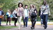 A group of male and female postgraduate students walking through the park