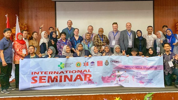 Group of Indonesian and British researcher standing in front of a banner showing, Emergency Sevices International Seminar.