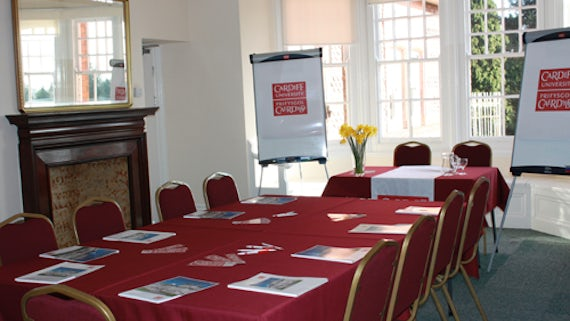 Room with table and chairs, laid with red tablecloth, papers on table, a table at front of room and flipcharts.