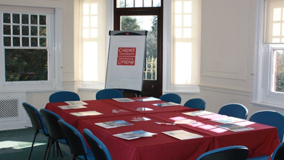 Room with table and chairs, laid with red tablecloth, papers on table, a table at front of room and flipchart.