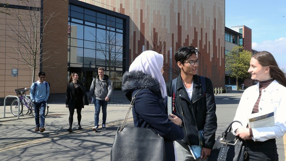 Three students standing outside of a building