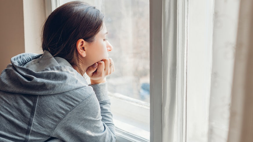 Stock image of person looking out of the window