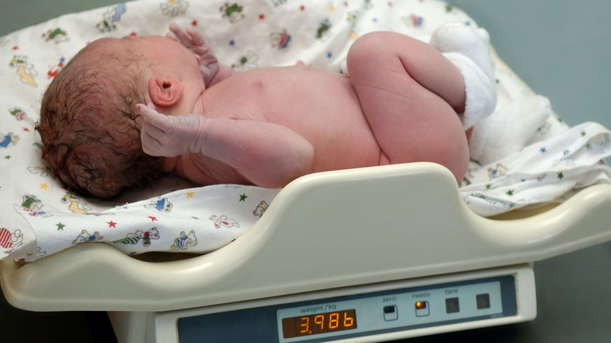 Stock image of newborn baby being weighed