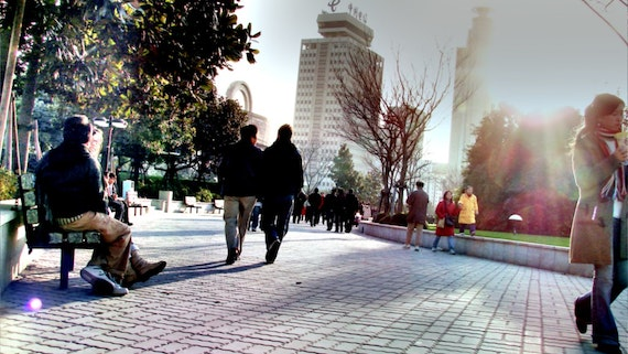 Friends walk together at a city square in China