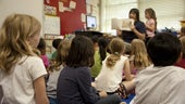 children on classroom floor listening to teacher