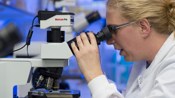 Female scientist looking into microscope