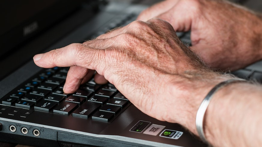 Photograph of a person's hands typing on a laptop