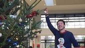 Image of student placing a bauble on the Christmas tree