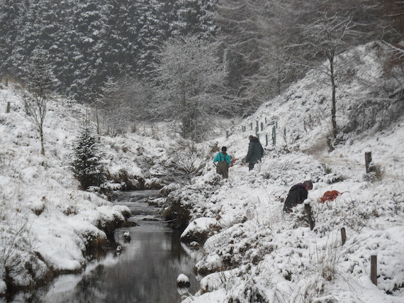Stream with snow on banks and people collecting biological samples
