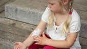Young girl applying cream to forearm