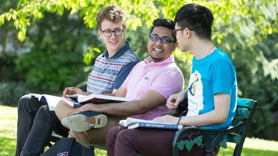 Three male students sitting on a bench, talking and smiling in a sunny park