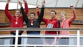 Four members of Cardiff University rowing quad smiling and waving, wearing their medals