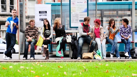 Students sat at a bus stop