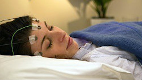 Woman lying a bed with wires attached to her face.