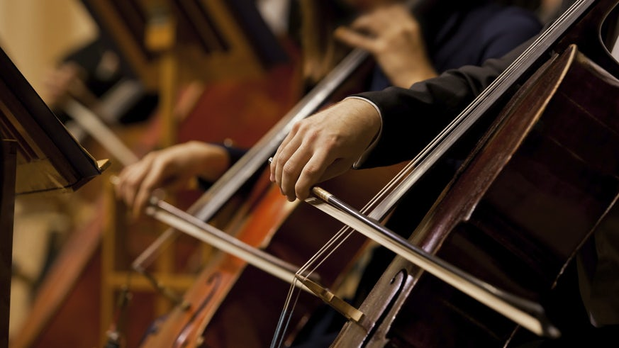 3 violins being played in an orchestra