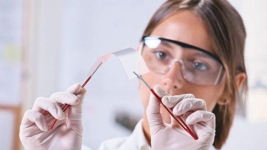 Lab tech in white coat holding up graphene