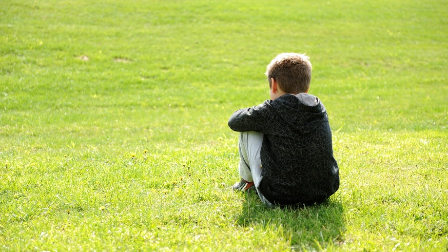 Image of a child sat alone in a field