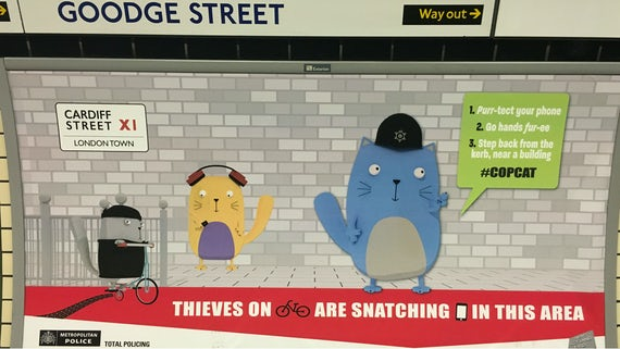 Image of a cartoon cat warning people about crime, on the wall of Goodge Street underground station.