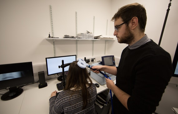 A researcher applies brain stimulation to a participants head
