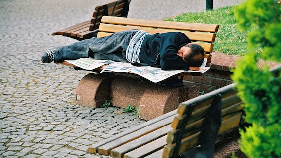 Image of homeless man sleeping on a bench
