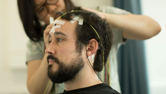 A female researcher places EEG electrodes on male participant's head