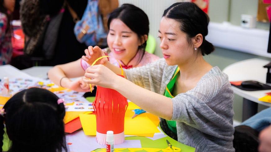 Chinese tutors help children to make Chinese lanterns