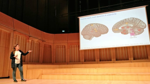A female keynote speaker gives a talk about the brain at the MEG UK research conference hosted by CUBRIC