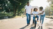 Child learning to ride a bike with her parents