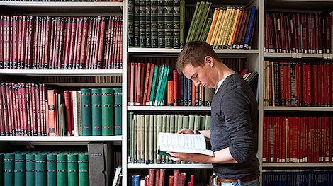 Male student reading in front of a wall of books