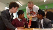 Male volunteer shows three year seven boys a sword as an example of a historical artifact.