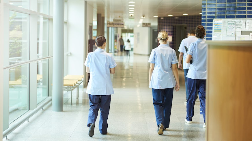 Nurses walking down corridor stock image