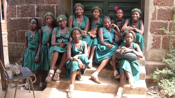 Group of school girls in uniform sitting on steps in Sierra Leone