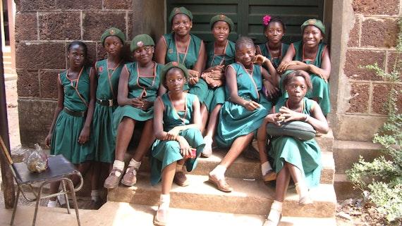 Grŵp o ferched ysgol mewn gwisg ysgol yn eistedd ar gamau yn Sierra Leone.